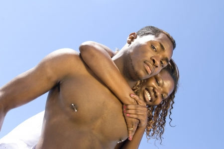 An African American couple embrace during an outdoor event at the beach.  photo