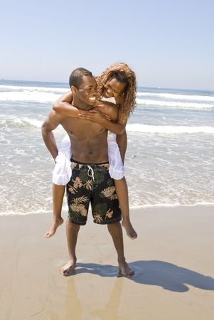 nipple piercing: A happy, cheerful African American couple frolics on the beach in a loving embrace Stock Photo