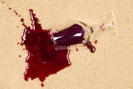 carpet stain: A glass of spilled wine on brand new carpet is sure to leave a stain. Stock Photo