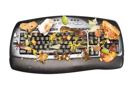 A keyboard covered with food remnants. We all know that we are guilty of eating while workig on our computers and how food finds its way onto the keyboard, causing crunchy perforamance and dirty computer equipment.