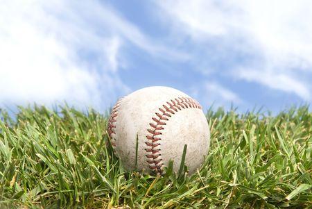 baseball ball: A baseball lying in a green grass field with a beautiful sky.