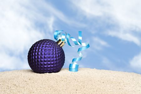 inference: A purple Christmas ornament with blue ribbon on a sandy beach with bright blue skys and puffy white cloouds.  Good image for any Christmas holiday outdoor inference. Stock Photo