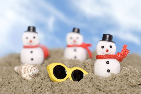inferences: Christmas ornament snowmen make their way across the beach in a tropical theme with a shell and sunglasses.  Good use for Christmas holiday tropical inferences and outdoor themes. Stock Photo