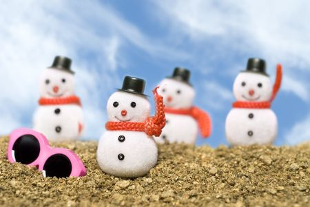 inference: Christmas snowmen ornaments on a gravel beach with pink sunglasses to cast a tropical summer theme.  Good for a tropical, outdoor Christmas inference.