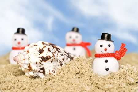inferences: Christmas ornament snowmen make their way across the beach in a tropical theme. Good use for Christmas holiday tropical inferences and outdoor themes. Stock Photo