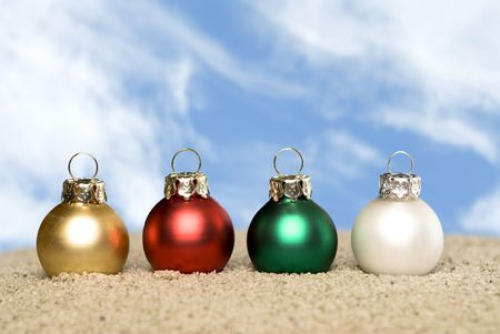 Four Christmas ornaments on a sandy beach poised against a blue sky with white, puffy clouds.