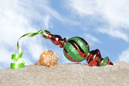 poised: A beautiful Christmas ornament with green ribbon on a sandy beach and poised against a blue sky with white puffy clouds. Stock Photo