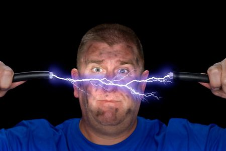 An electrician playes with some live wires, causing an arc of electricity and charring the mans face. photo