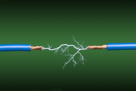 An electrical arc crossing two blue, copper wires on a green and black gradient background. photo