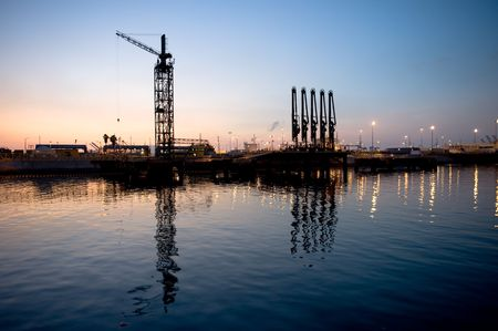 unloading: A tanker loading and unloading dock with hoist cranes and oil pumps in an industrial harbor during sunset.