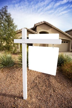 A home for sale has a for sale sign that is blank for copy space.  Good image for designers to place text inferences such as for sale, foreclosure; sold, bank owned, etc.  Focus is on sign and the house is slightly blurred. Imagens