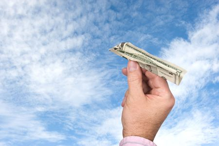 tosses: A man tosses a paper plane made of a five dollar bill into a blue sky with white, puffy clouds.