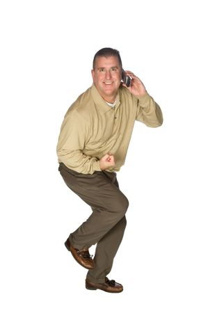 A man gets excited after receiving positive news over his cell phone and makes a bodily expression as if saying, oh yea! photo