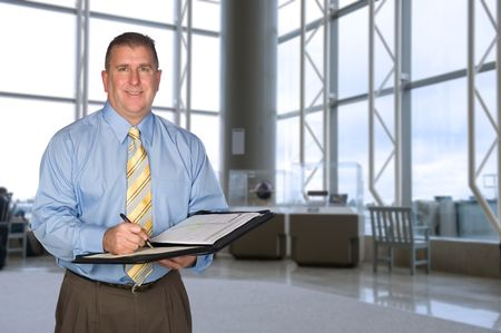 A mature business man taking notes in a large lobby photo