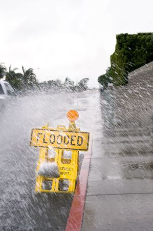 A car kicks up a pool of rainwater over a street floded sign during bad, rainy weather.