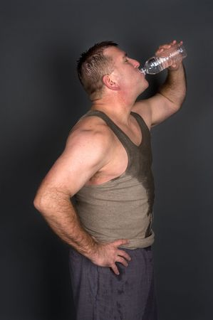 A muscular man drinks a bottle of water after a sweaty, hard workout and exercise regime.