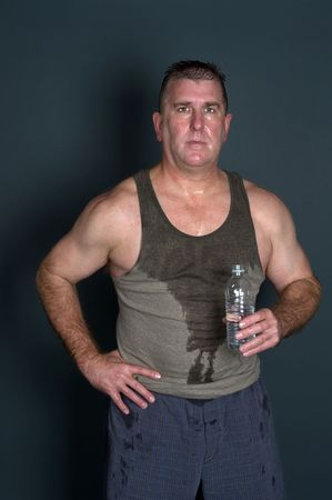A muscular middle aged man stands sweaty after a hard workout and exercise regime and gets ready to consume more bottled water.