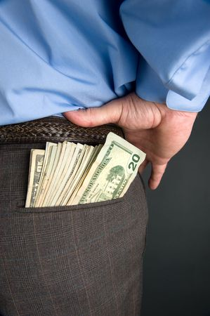 putting money in pocket: A businessman with cash sticking out of back pocket.