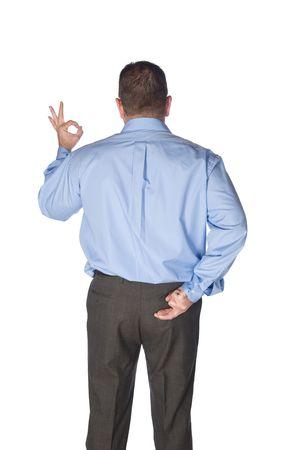 comunicacion no verbal: Un hombre de negocios dando la se�al bien tiene sus dedos cruzados detr�s de su espalda como si ser un mentiroso o enga�ar a su cliente. Foto de archivo