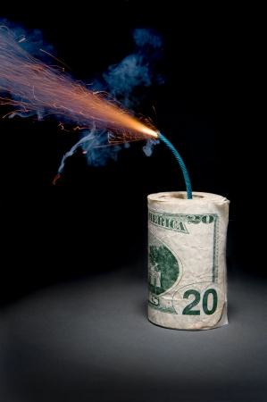 A roll of cash made into a dynamite stick has a lighted fuse throwing smoke and sparks before it explodes. photo