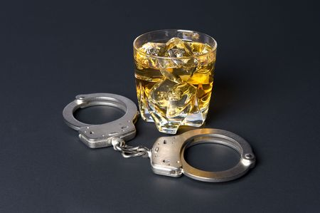 restraints: A pair of handcuffs next to a glass of whiskey infers that drinking and driving is illegal.