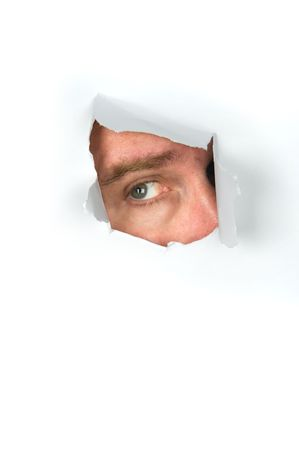 A man peers through a torn paper hole. Stock Photo - 6525282