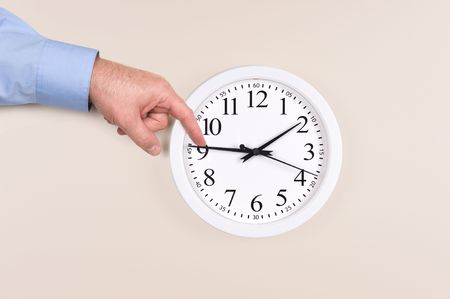 reversing: A man uses his finger to push back the time on a clock to daylight savings time