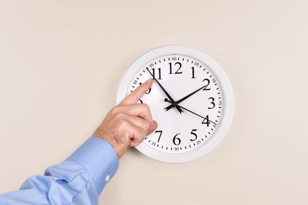 counterclockwise: A man changes the time on a clock, moving it forward in time, spring forward. Stock Photo