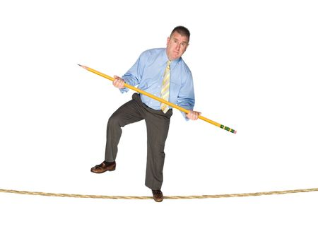 inferences: A businessman balancing on a tightrope using a giant pencil as a balancing pole.  Image is good for business risk and success inferences.