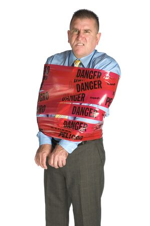 unkind: An angry businessman wrapped in danger tape as a warning to coworkers snarls as a result of stress and frustration