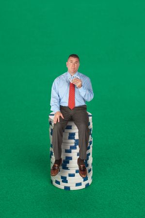 A businessman sitting on a stack of poker chips with a five card hand dealing with risk, success, chance or strategy. photo