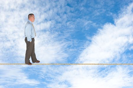A businessman walks across a tightrope contemplating success, risk, vision and the way forward. Stock Photo