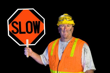 A dirty, greasy utility construction worker with a yellow hard hat, safety goggles, and a reflective orange vest holding up a warning slow sign. photo