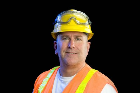 A construction utility worker wearing protective safety equipment including a hard hat, safety goggles and a reflective orange vest smiles against a black background.
