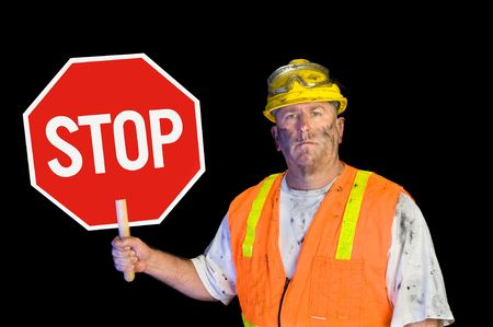 road shoulder: A dirty, grungy, greasy utility construction worker with hard hat, orange vest and eye protection holds up a stop sign.  Isolated on black and can be used as a design element.