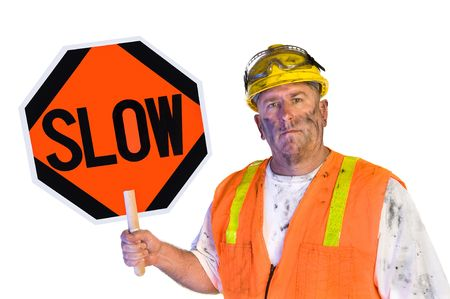 A dirty, grungy, greasy utility construction worker with hard hat, orange vest and eye protection holds up a slow sign.  Isolated on white and can be used as a design element. photo