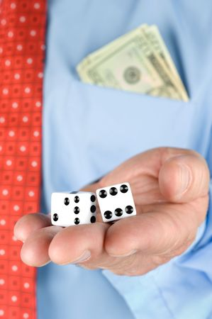 inferences: A businessman with a pocket full of cash holds a pair of dice while gambling.  Image is good for most business inferences for risk, chance, gambling and success.