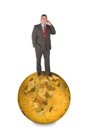 An international businessman standing on a world globe while talking on his cell phone. Stock Photo - 6862704