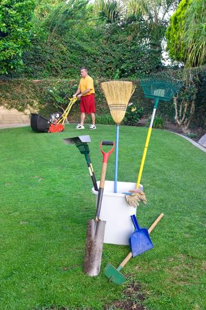 mows: A gardner mows a lawn and prepares to conduct other gardening work