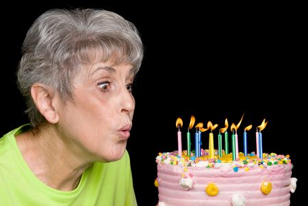 one senior adult woman: A senior female blows out candels on a cake.  Ideal for birthday, anniversary or any other celebration inference.