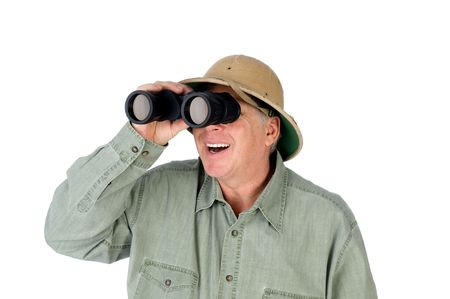 pith: A mature adult man wearing a pith helmet looks through a pair of binoculars. Stock Photo