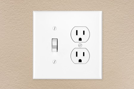 A brand new modern electrical toggle light switch and power outlet on a freshly painted wall. photo