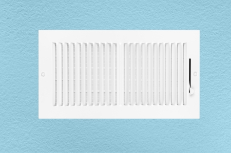 louvered: A new heating and air conditioning wall vent on a blue textured wall.