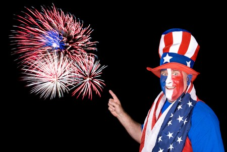 A patriotic man dressed up in red, white and blue points to fireworks in the sky. Stock Photo - 7443087