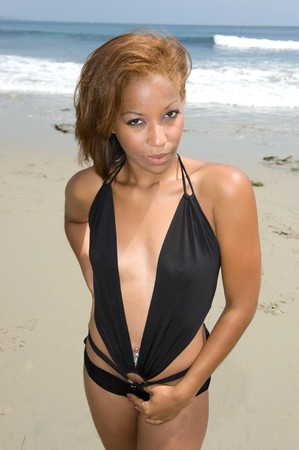A beautiful African American woman wearing a skimpy bikini at the beach. photo