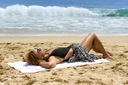 An African American woman relaxes at the beach while sunbathing.