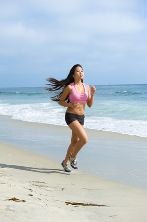 A beautiful Asian woman exercises by jogging along the shoreline of a beach. photo