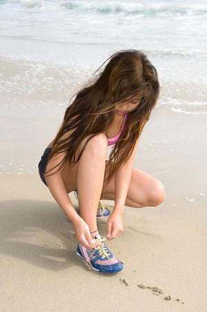 en cuclillas: Un hermoso, joven libros de Asia en la playa se arrodilla en la arena como ella lazos de sus zapatos.