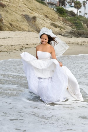 A happy Asian bride wearing her wedding dress and veil wades through the surf zone and a remote beach just after her wedding. photo