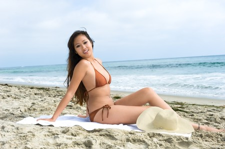 An attractive Asian woman relaxes at the beach while sunbathing during a beautiful day. Stock Photo - 7443098